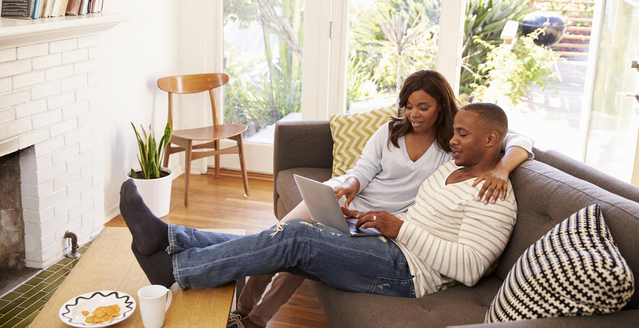 Couple sitting in living room looking at laptop.